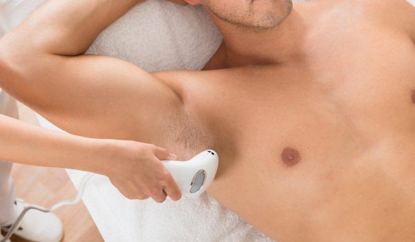 schoonheidsspecialiste die een laserontharingbehandeling uitvoert op een man